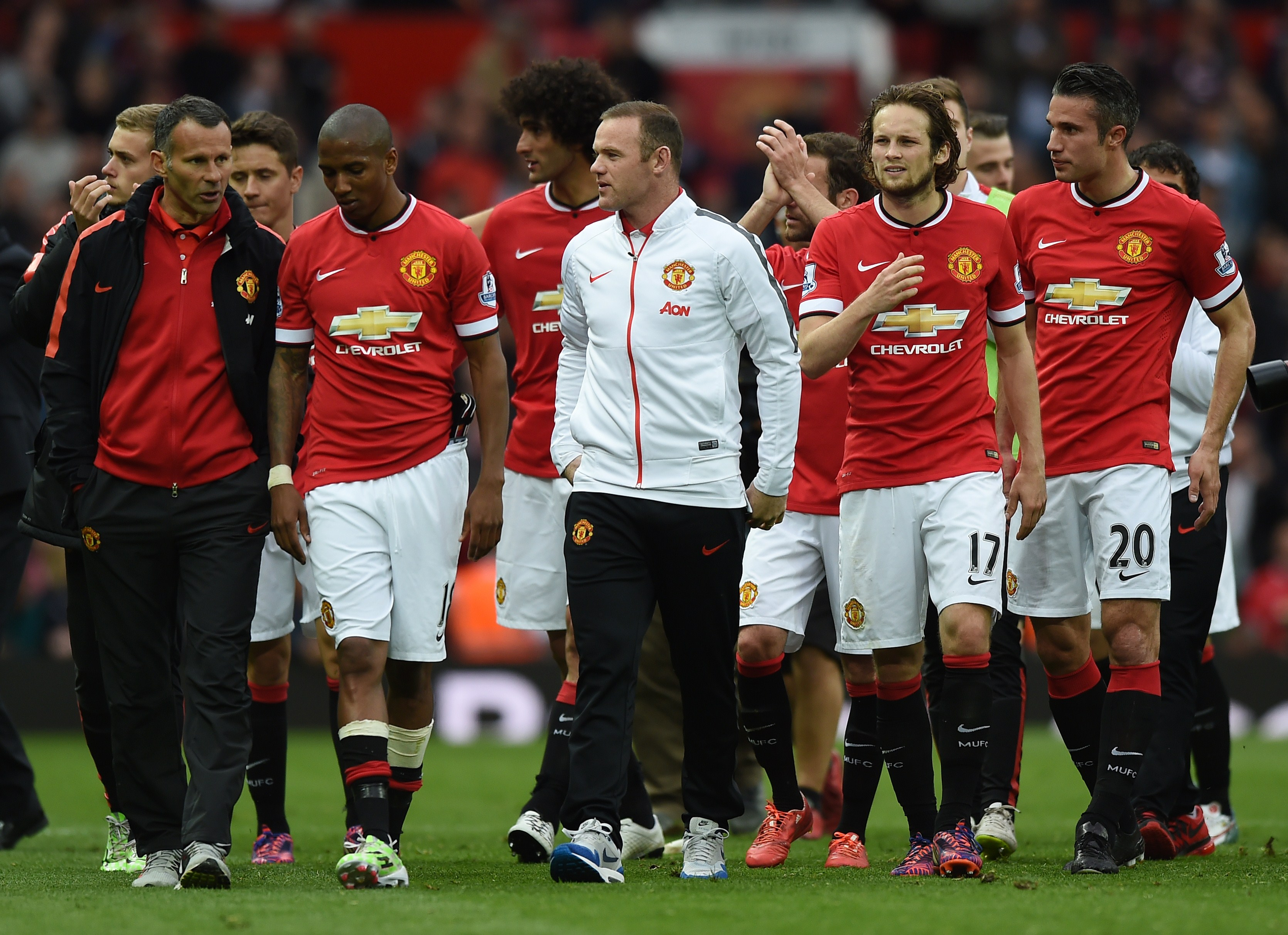 """Manchester United's English striker Wayne Rooney (C) walks on the pitch with teammates after the English Premier League football match between Manchester United and Arsenal at Old Trafford in Manchester, northwest England, on May 17, 2015. AFP PHOTO / PAUL ELLIS RESTRICTED TO EDITORIAL USE. No use with unauthorized audio, video, data, fixture lists, club/league logos or """"live"""" services. Online in-match use limited to 45 images, no video emulation. No use in betting, games or single club/league/player publications"""